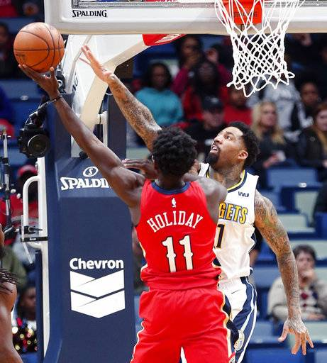 New Orleans Pelicans guard Jrue Holiday (11) goes to the basket against Denver Nuggets forward Wilson Chandler in the first half of an NBA basketball game in New Orleans, Wednesday, Dec. 6, 2017.