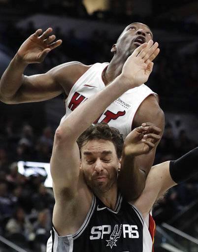 Miami Heat center Bam Adebayo, top, and San Antonio Spurs center Pau Gasol, bottom, jockey for position for a rebound during the first half of an NBA basketball game Wednesday, Dec. 6, 2017, in San Antonio.
