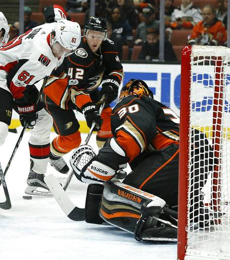 Ottawa Senators right wing Mark Stone (61) looks for the puck as Anaheim Ducks goalie Ryan Miller (30) and defenseman Josh Manson (42) defend during the first period of an NHL hockey game in Anaheim, Calif., Wednesday, Dec. 6, 2017.