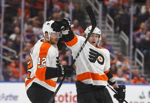 Philadelphia Flyers' Michael Raffl (12) and Jakub Voracek (93) celebrate a goal against the Edmonton Oilers during the third period of an NHL hockey game Wednesday, Dec. 6, 2017, in Edmonton, Alberta. (Jason Franson/The Canadian Press via AP)