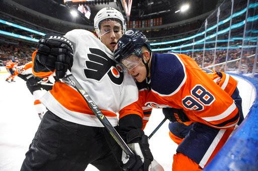 Philadelphia Flyers' Valtteri Filppula, left, and Edmonton Oilers' Jesse Puljujarvi (98) battle in the corner during the second period of an NHL hockey game Wednesday, Dec. 6, 2017, in Edmonton, Alberta. (Jason Franson/The Canadian Press via AP)