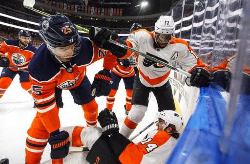 Philadelphia Flyers' Sean Couturier (14) is checked by Edmonton Oilers' Darnell Nurse (25) as Wayne Simmonds (17) checks Darnell Nurse (25) during the first period of an NHL hockey game Wednesday, Dec. 6, 2017, in Edmonton, Alberta. (Jason Franson/The Canadian Press via AP)