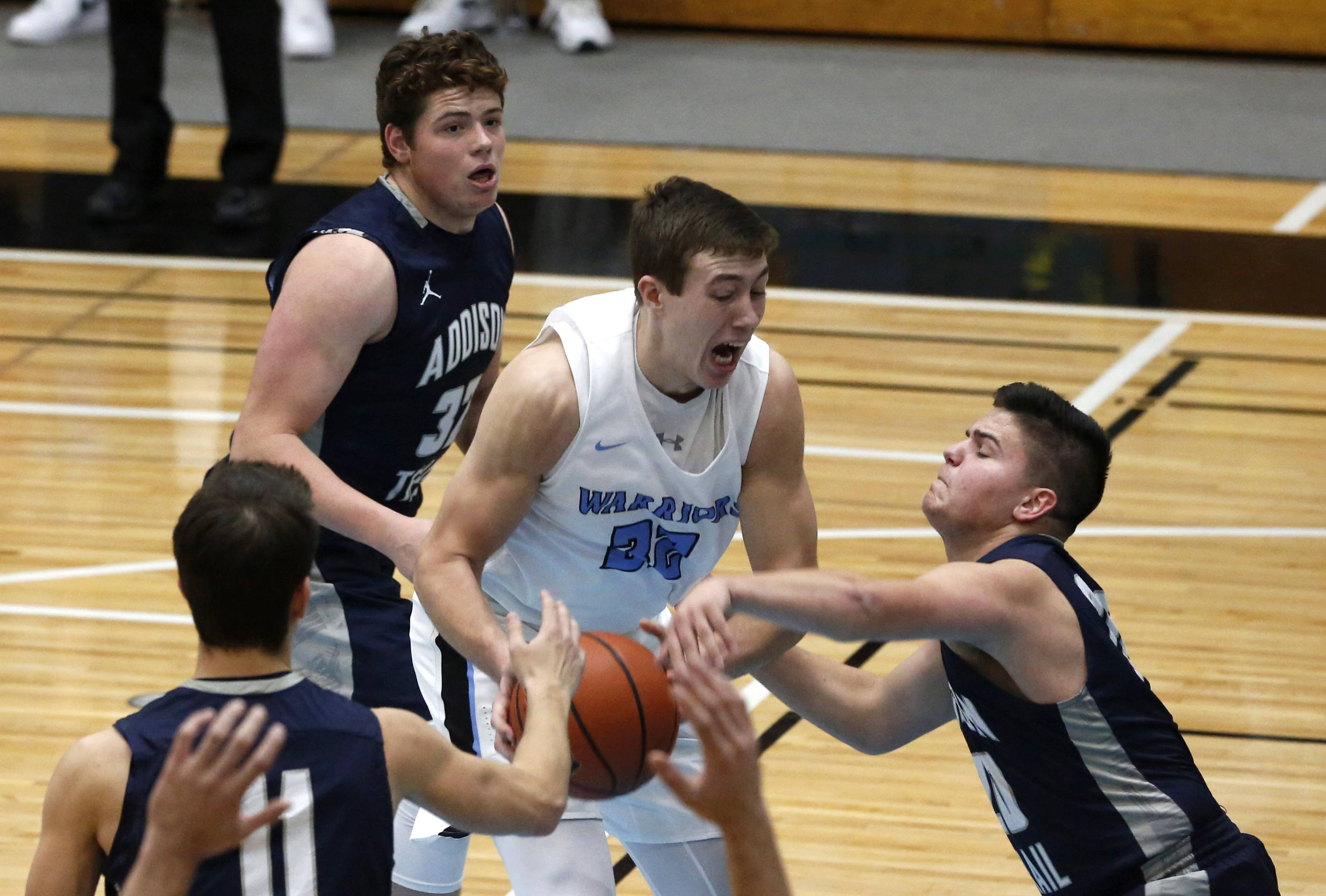 Willowbrook's Ethan Schuemer (32) drives to the basket against Addison Trail's Connor Palesch, right.