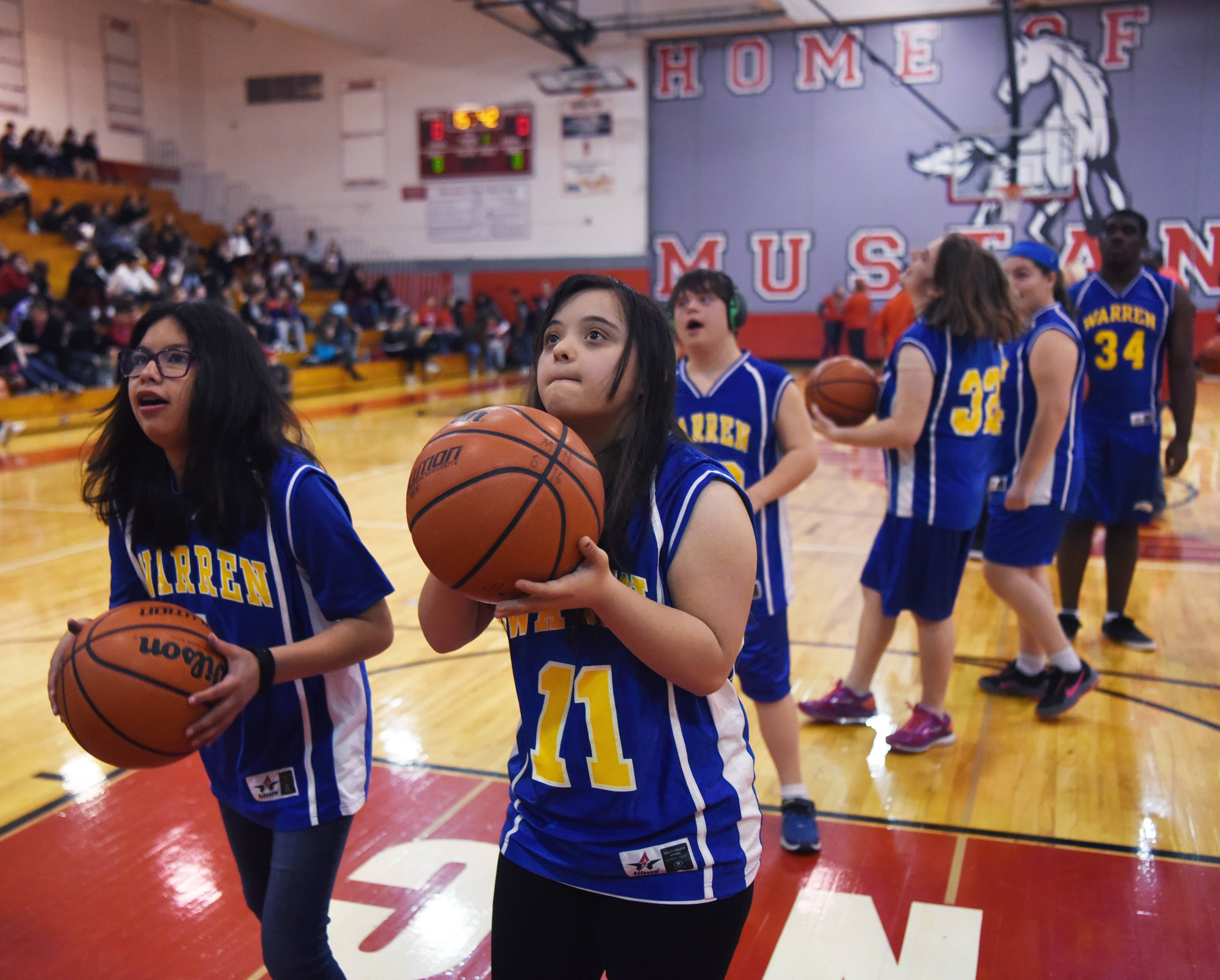 Warren Township High School's Keisha Sievers, left, and Saja Abdel-Jaber practice before Friday's basketball game for adaptive physical education students at Mundelein High School.
