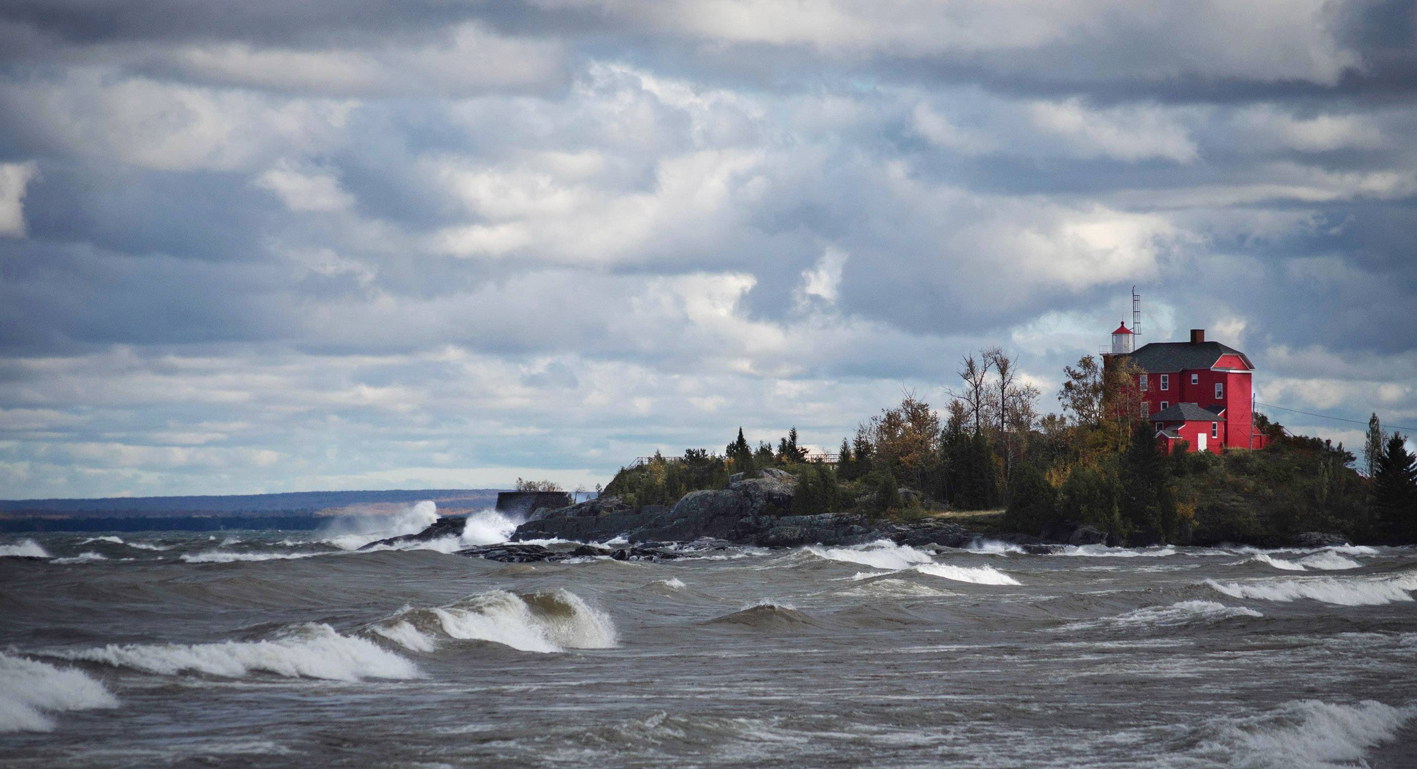 Waves crash near a beautiful red house along the beach of Lake Superior.