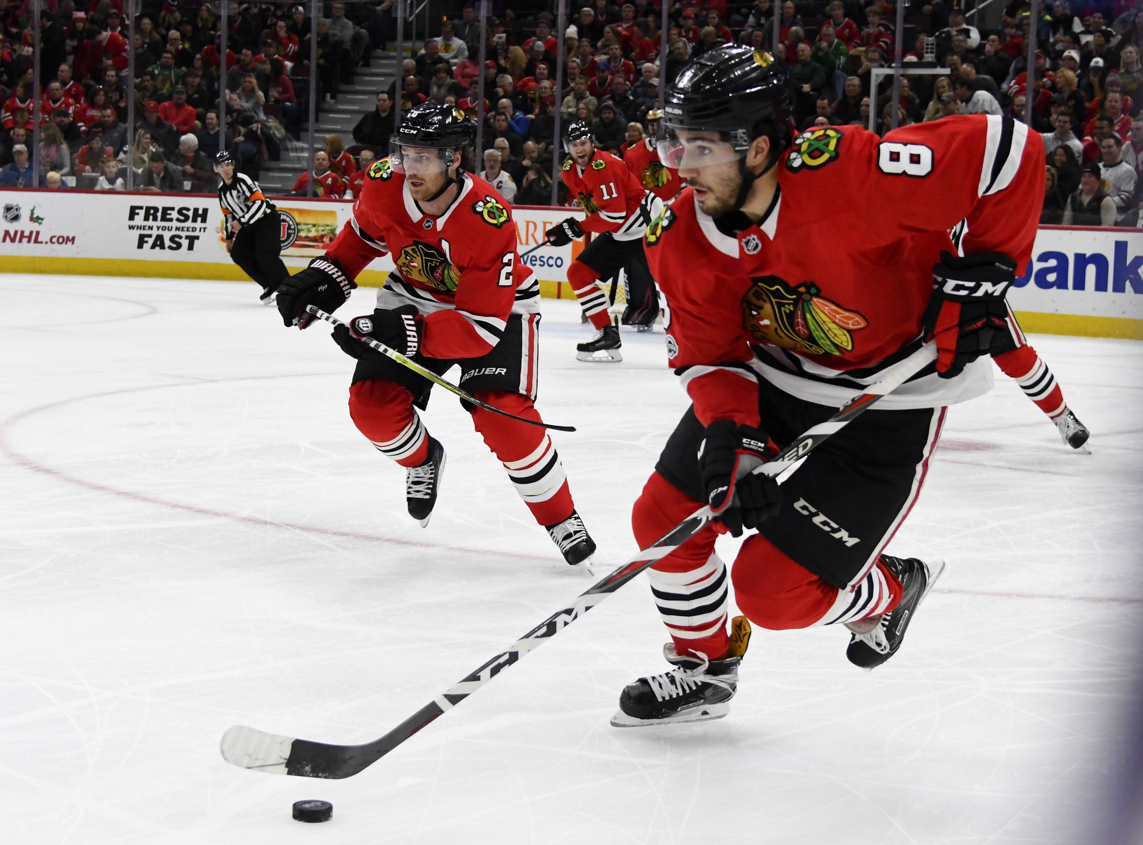 Chicago Blackhawks center Nick Schmaltz (8) advances the puck as Duncan Keith (2) looks on against the Buffalo Sabres during the first period of an NHL hockey game Friday Dec. 8, 2017, in Chicago. (AP Photo/Matt Marton)