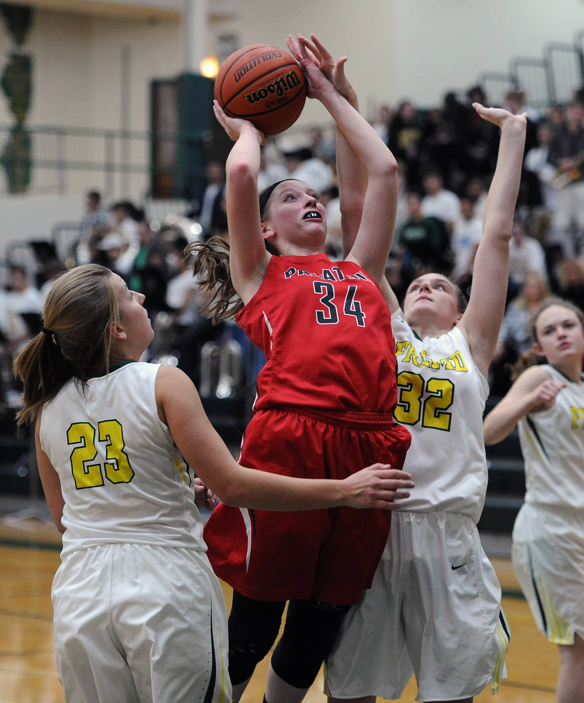 Palatine's Sydney Rzepka squeezes between Fremd defenders Emily Klaczek and Olivia Hill for a shot.