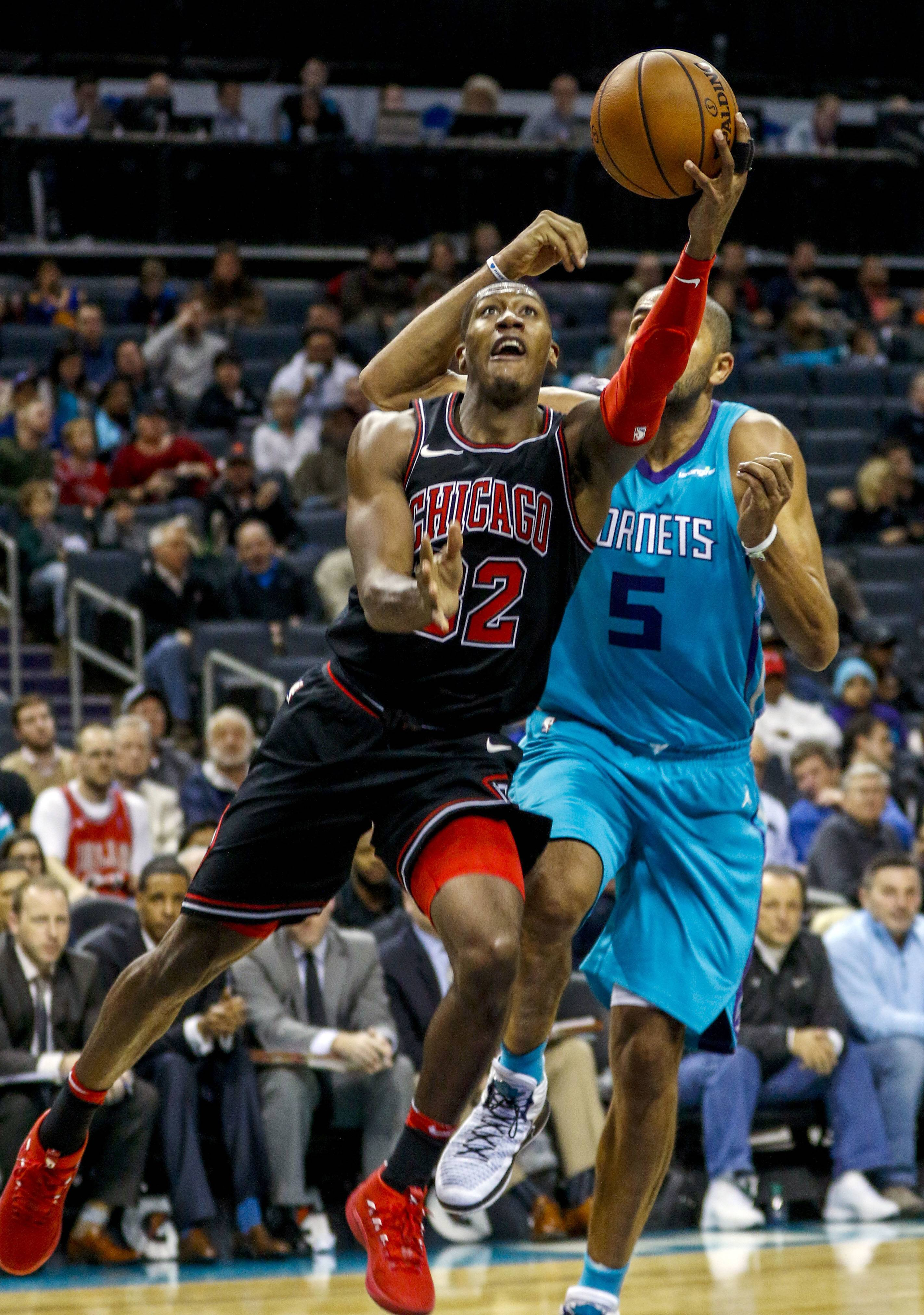 Chicago Bulls guard Kris Dunn, left, drives to the basket past Charlotte Hornets guard Nicolas Batum in the second half in Charlotte, N.C., Friday. Lauri Markkanen scored 24 points and Dunn added 20 as the Bulls ended their 10-game losing streak with a 119-111 overtime victory at Charlotte. Nikola Mirotic made his season debut and scored 6 points.