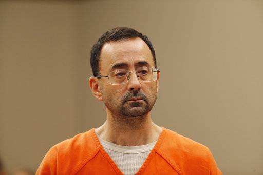 FILE - In this Nov. 22, 2017, file photo, Dr. Larry Nassar, appears in court for a plea hearing in Lansing, Mich. Nassar, an elite Michigan sports doctor who possessed child pornography and assaulted gymnasts, was sentenced Thursday, Dec. 7, 2017, to 60 years in federal prison in one of three criminal cases that ensure he will never be free again. (AP Photo/Paul Sancya, File)