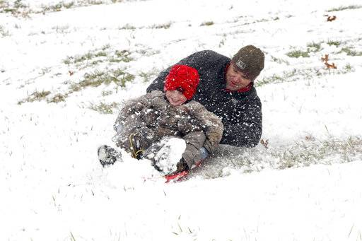 Allen and Cooper Alexander, 4, spin around while sledding down a hill Friday Dec. 8, 2017, in Vicksburg, Miss. Heavy snow fell across several Southern states Friday. (Courtland Wells/The Vicksburg Post via AP)