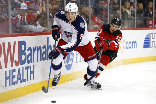 Columbus Blue Jackets defenseman Zach Werenski (8) controls the puck in front of New Jersey Devils center Nico Hischier during the second period of an NHL hockey game, Friday, Dec. 8, 2017, in Newark, N.J. The Blue Jackets won 5-3. (AP Photo/Adam Hunger)