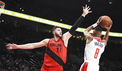 Washington Wizards guard Tim Frazier drives to the basket on Portland Trail Blazers center Jusuf Nurkic during the first half of an NBA basketball game in Portland, Ore., Tuesday, Dec. 5, 2017. (AP Photo/Steve Dykes)
