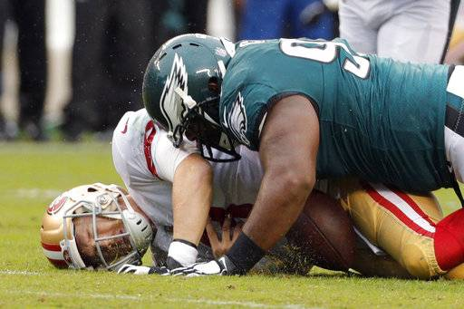 FILE - In this Oct. 29, 2017, file photo, San Francisco 49ers' C.J. Beathard is sacked by Philadelphia Eagles' Fletcher Cox during the first half of an NFL football game, in Philadelphia. Fletcher Cox and Aaron Donald are two of the NFL's best interior defensive linemen, sharing an agent and a passion for disruptive play. While Jared Goff and Carson Wentz are getting most of the attention before the Rams (9-3) host the Eagles (10-2), Cox and Donald will try to overshadow that showdown with their own feats. (AP Photo/Chris Szagola, File)