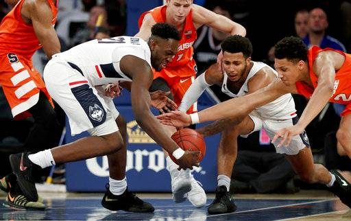 Connecticut forward Mamadou Diarra (21) and guard Jalen Adams and Syracuse forward Matthew Moyer (2) scramble after a loose ball during the second half of an NCAA college basketball game Tuesday, Dec. 5, 2017, in New York. Syracuse won 72-63. (AP Photo/Julie Jacobson)