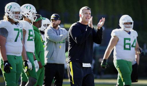 In this Sept. 26, 2017, photo, Oregon offensive coordinator Mario Cristobal gestures during practice in Eugene, Ore. Oregon will promote offensive coordinator Mario Cristobal to head coach, a person with direct knowledge of the situation told The Associated Press. The person spoke Friday, Dec. 8, 2017, on condition of anonymity because a deal and announcement were still being finalized. Cristobal was co-offensive coordinator and offensive line coach at Oregon this past season and was named interim coach on Tuesday when Willie Taggart left to become head coach at Florida State. (Andy Nelson/The Register-Guard via AP)/The Register-Guard via AP)