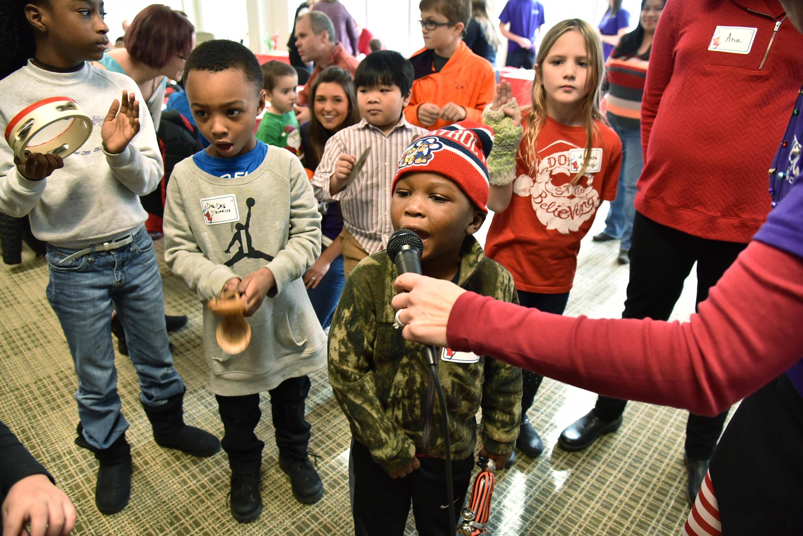 William Lackland, 5, of Elgin sings Christmas carols into a microphone held by speech therapist Rima Birutis as 176 children gather to visit with Santa Saturday at the Marianjoy Rehabilitation Hospital in Wheaton. William had brain surgery earlier in 2017 and had to relearn how to walk and talk, but now he loves to sing.