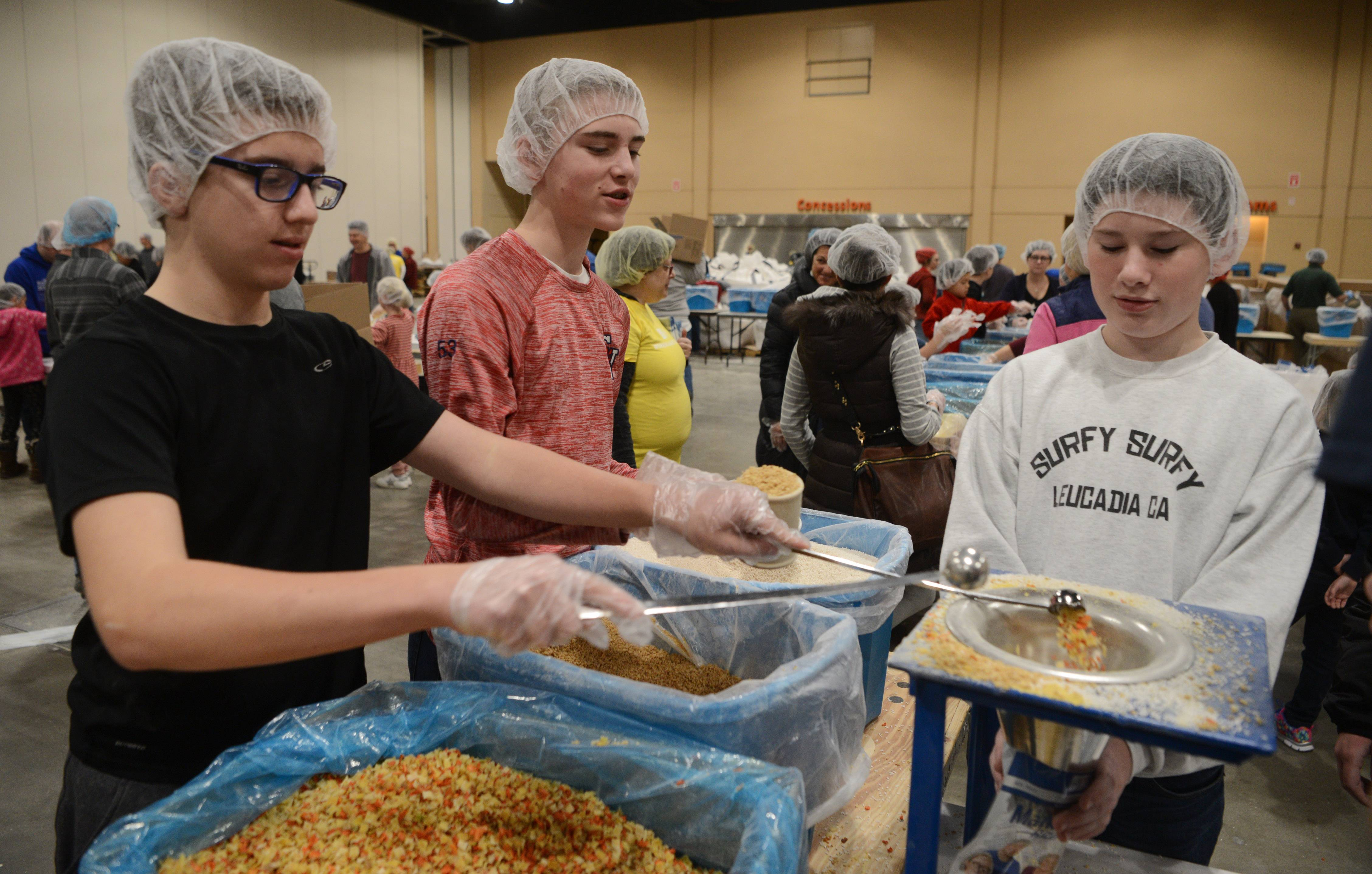 Left to right, Joseph Giuliani and Sean Bosshart, both 13-year-old eighth graders at St. Hubert Catholic in Hoffman Estates, and Sean Kenny, 14, from Our Lady of the Wayside School in Arlington Heights, help pack meals Sunday during the Hope Filled Holiday MobilePack event at the Renaissance Schaumburg Convention Center.