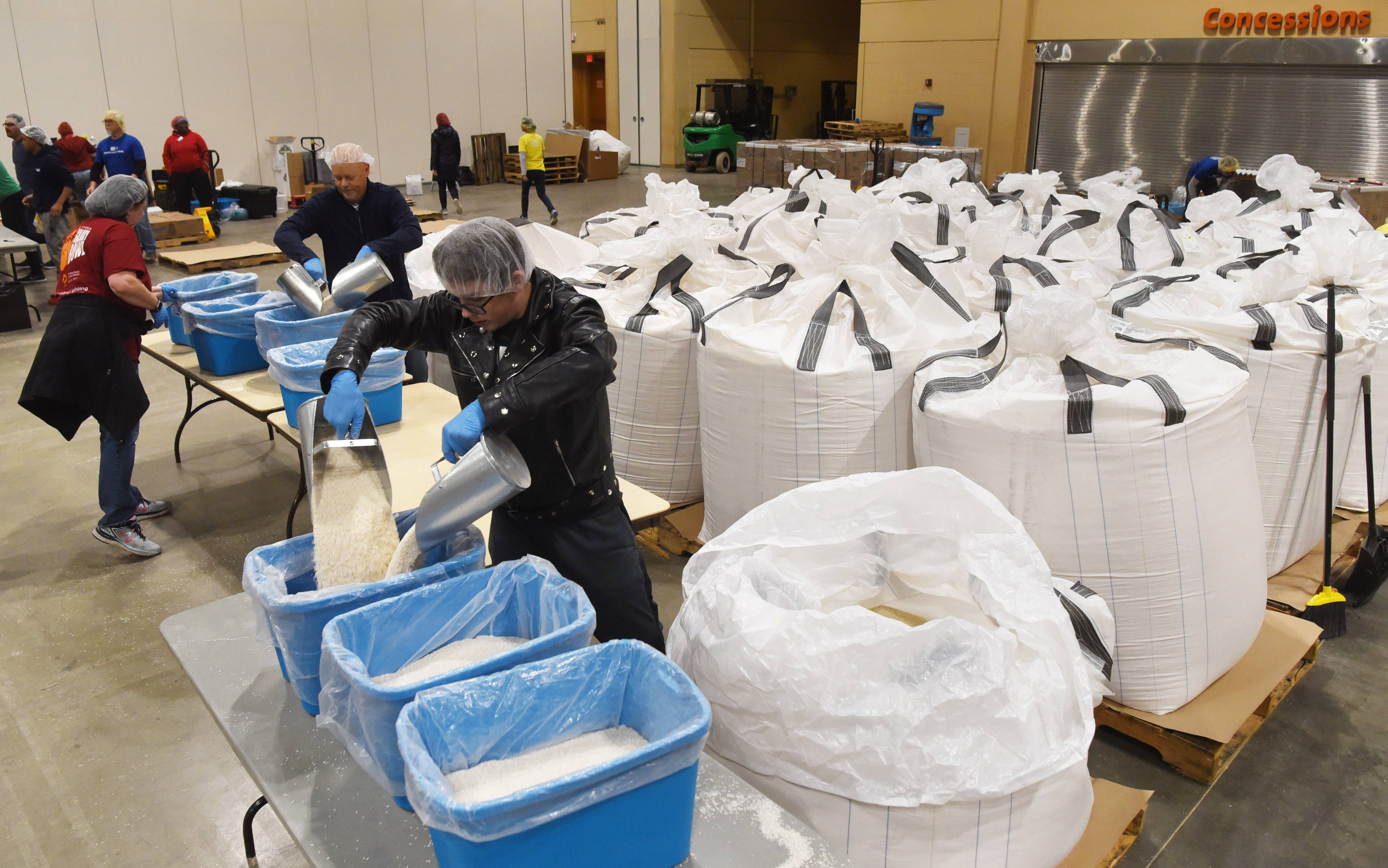 Ian Behnke of Elk Grove Village transfers rice from one-ton bags into bins Sunday during Feed My Starving Children's Hope Filled Holiday MobilePack event at the Renaissance Schaumburg Convention Center.