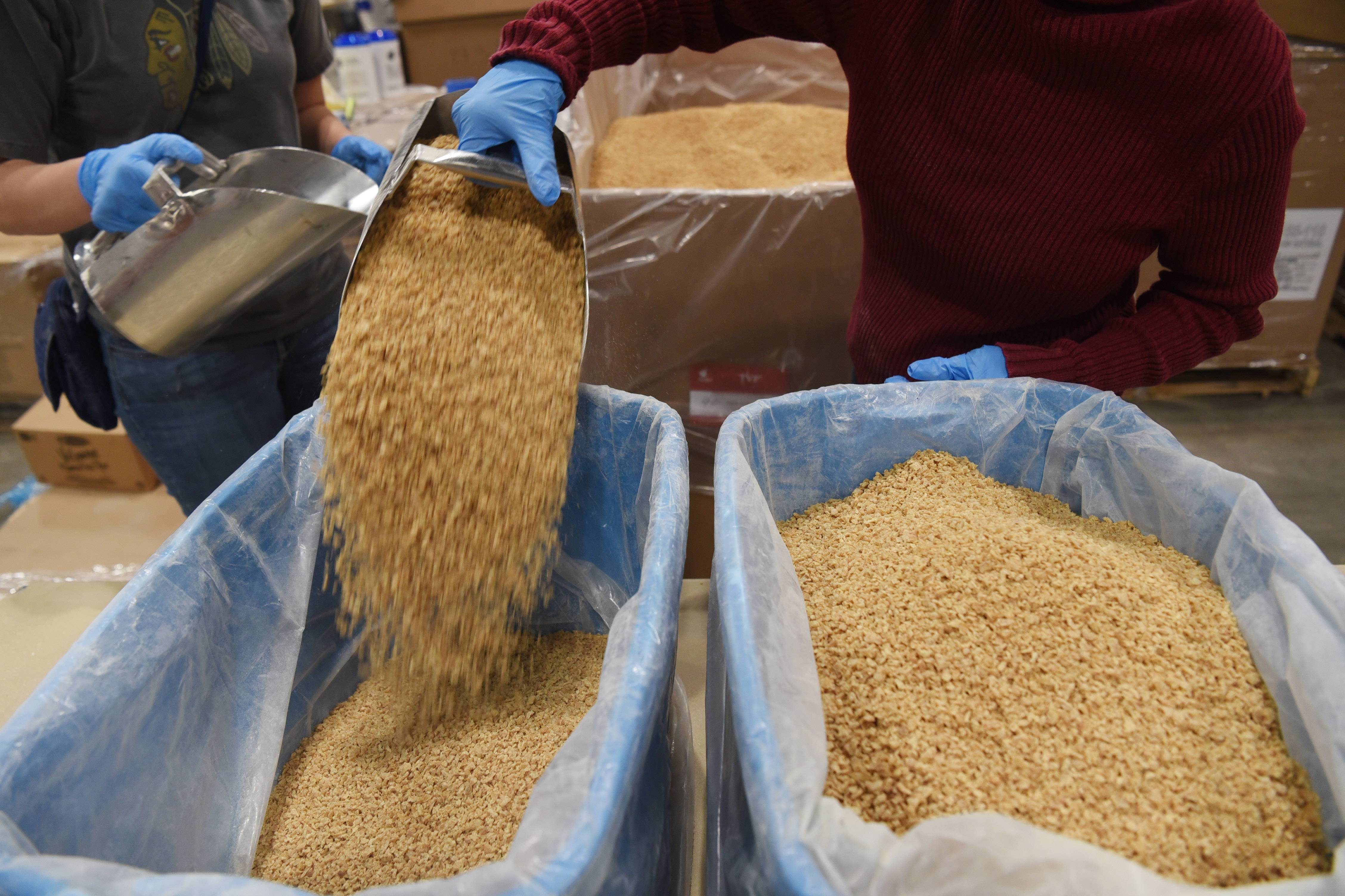 Soy product is transferred into bins Sunday during Feed My Starving Children's Hope Filled Holiday MobilePack event at the Renaissance Schaumburg Convention Center. Thousands of volunteers packed an estimated 1 million meals during the three-day event.