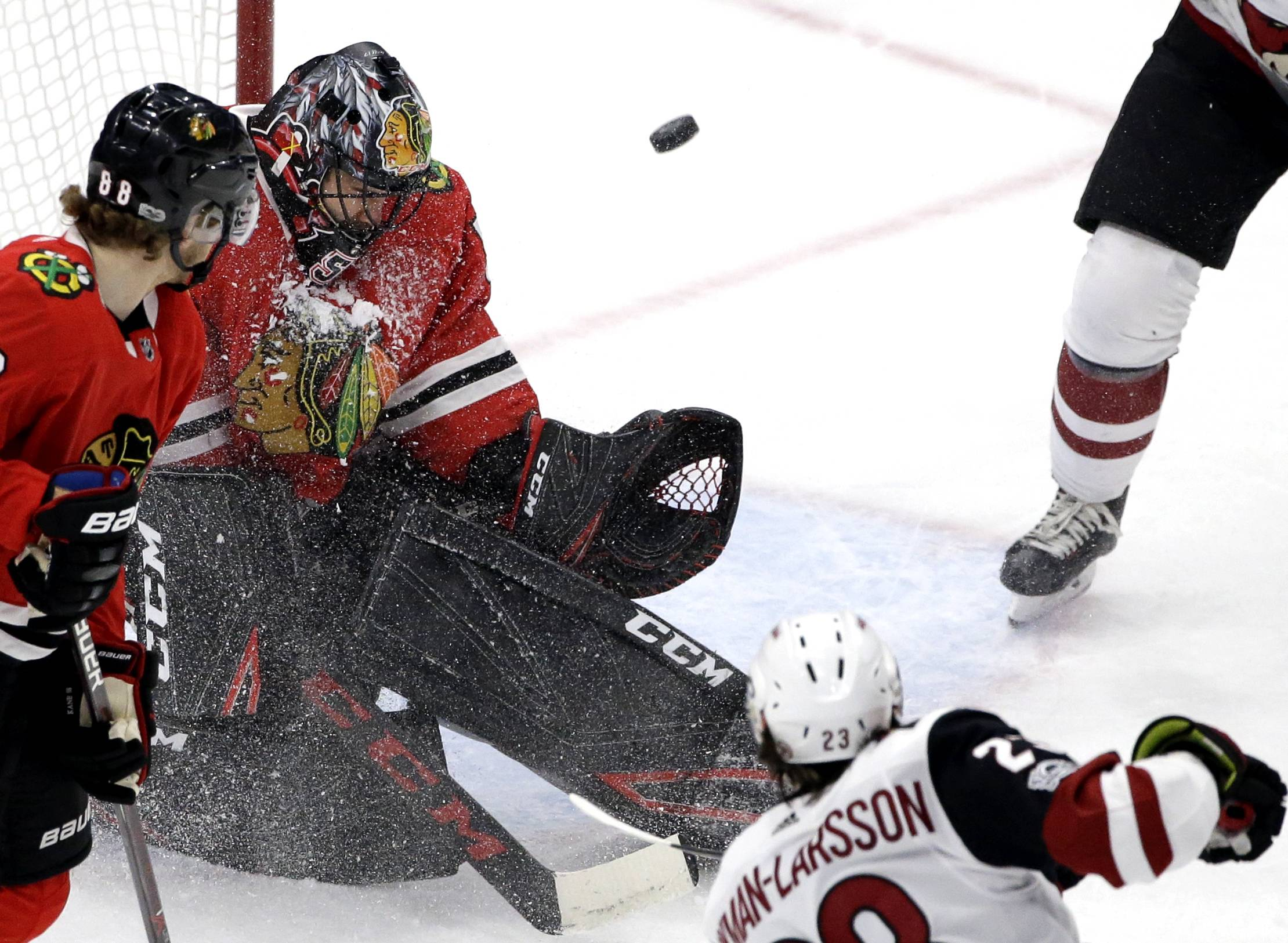 Chicago Blackhawks goalie Corey Crawford, second from left, blocks a shot by Arizona Coyotes defenseman Oliver Ekman-Larsson, lower right, during the second period of an NHL hockey game Sunday, Dec. 10, 2017, in Chicago. (AP Photo/Nam Y. Huh)
