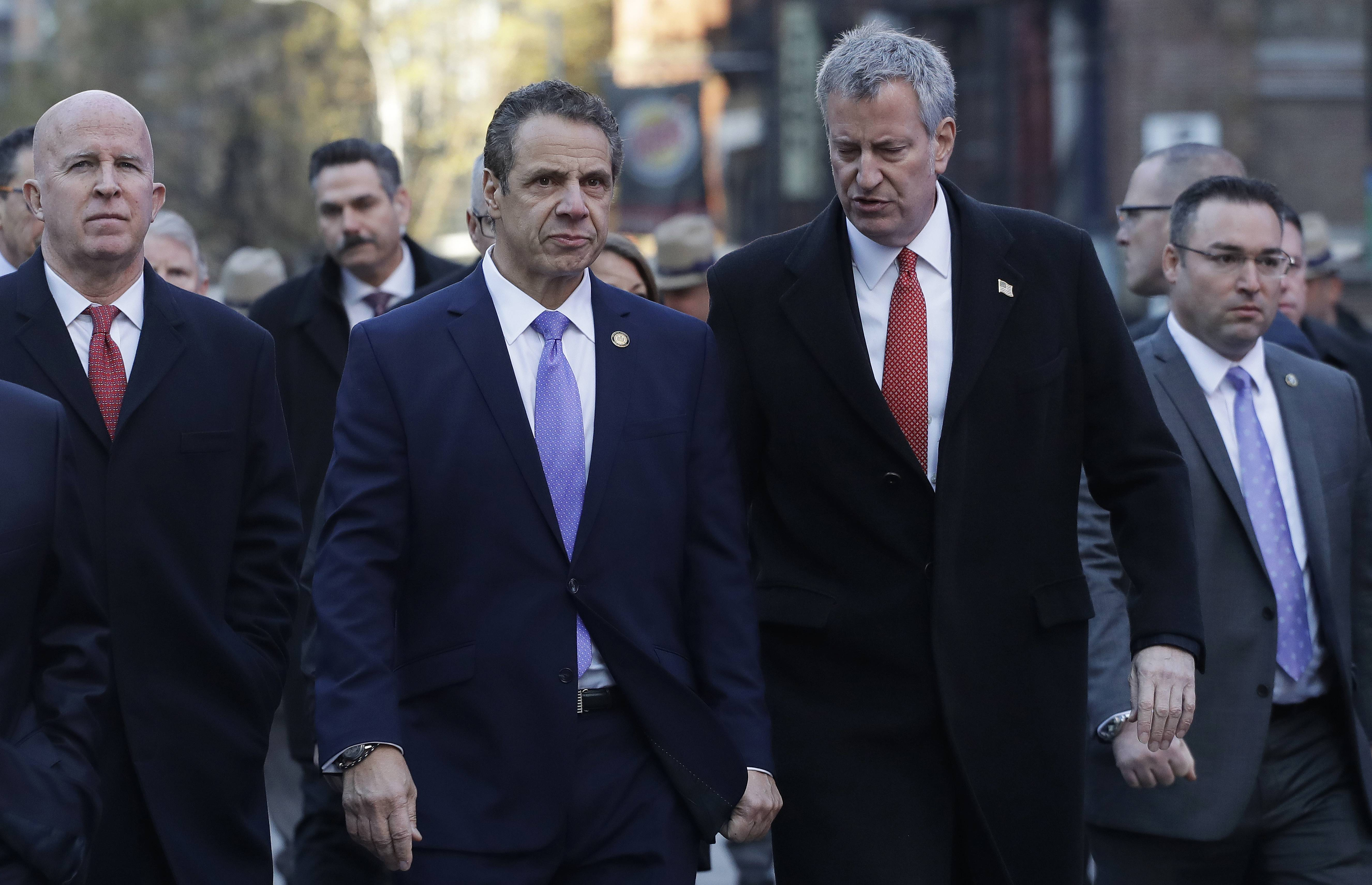 New York Gov. Andrew Cuomo, center, and Mayor Bill de Blasio arrive Monday for a news conference outside the Port Authority Bus Terminal in New York. Police Commissioner James O'Neill is at left.