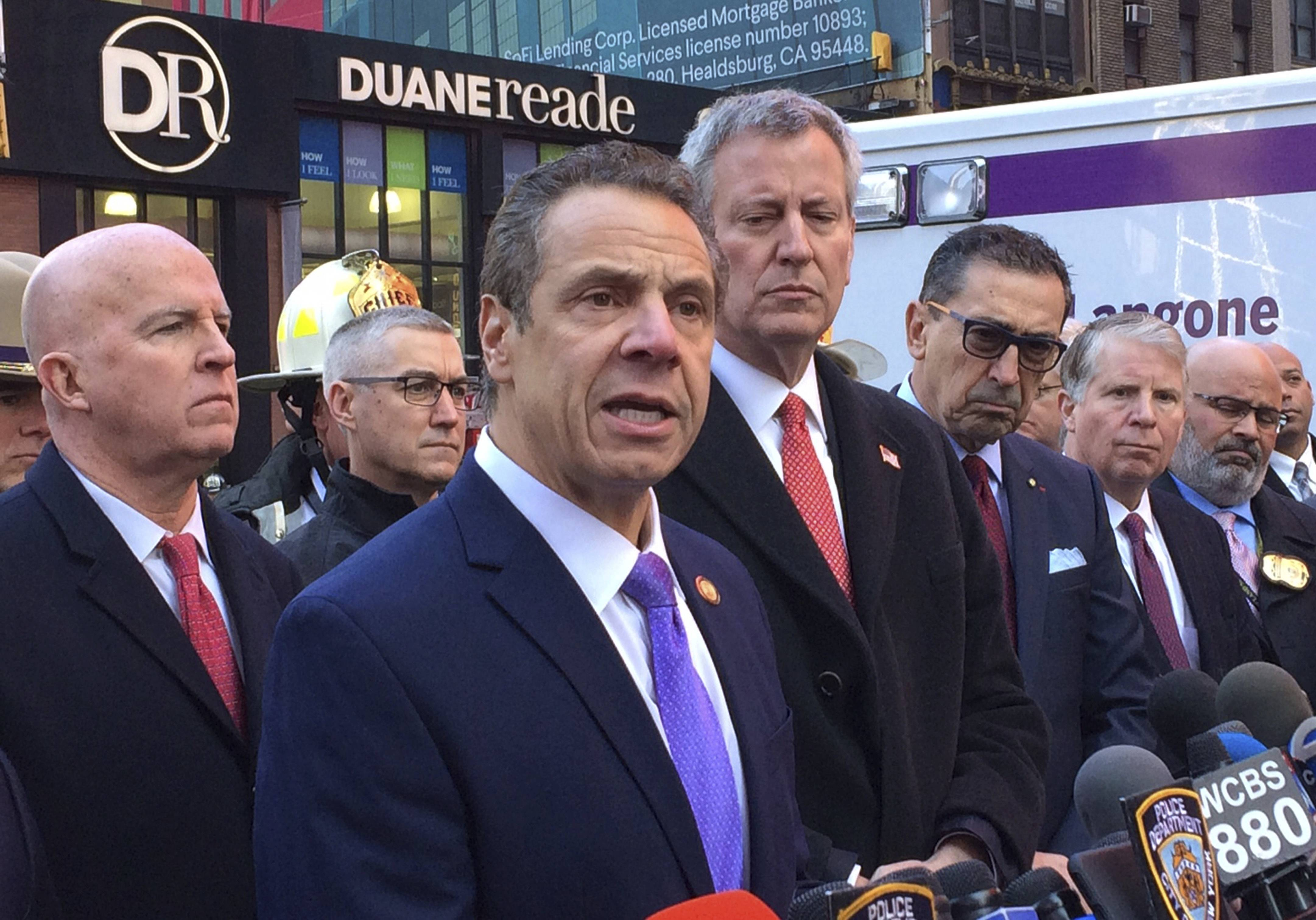 New York Gov. Andrew Cuomo speaks to members of the media Monday after a pipe bomb strapped to a man went off in a New York City subway near Times Square in New York. Mayor Bill de Blasio stands fourth from left.