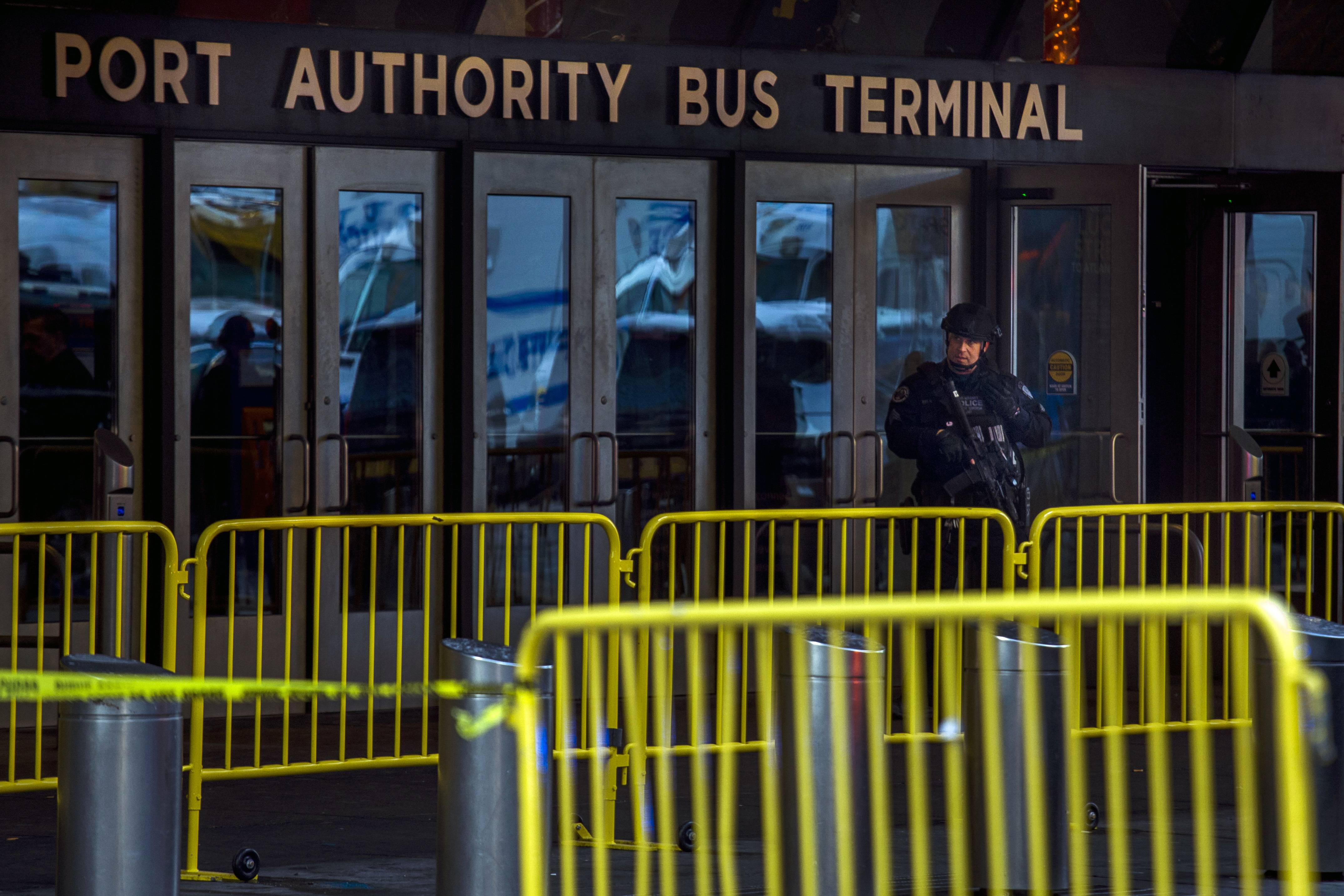 A police officer stands guard Monday in front of Port Authority Bus Terminal as law enforcement respond to a report of an explosion near Times Square in New York.