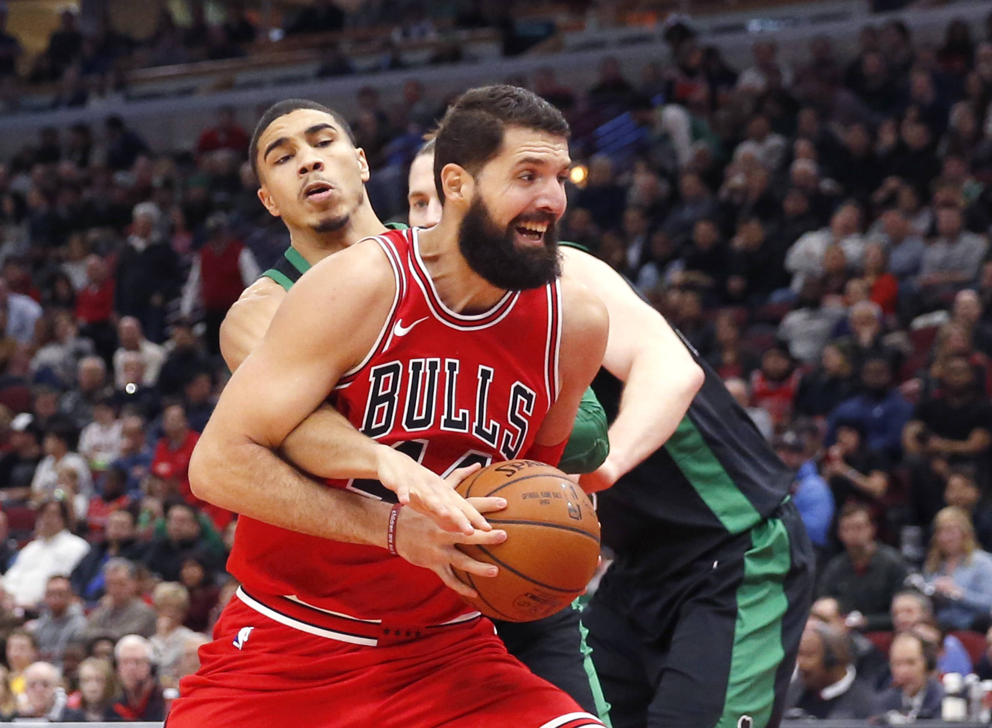 Chicago Bulls' Nikola Mirotic, right, is fouled by Boston Celtics' Jayson Tatum during the second half of an NBA basketball game Monday, Dec. 11, 2017, in Chicago. (AP Photo/Charles Rex Arbogast)