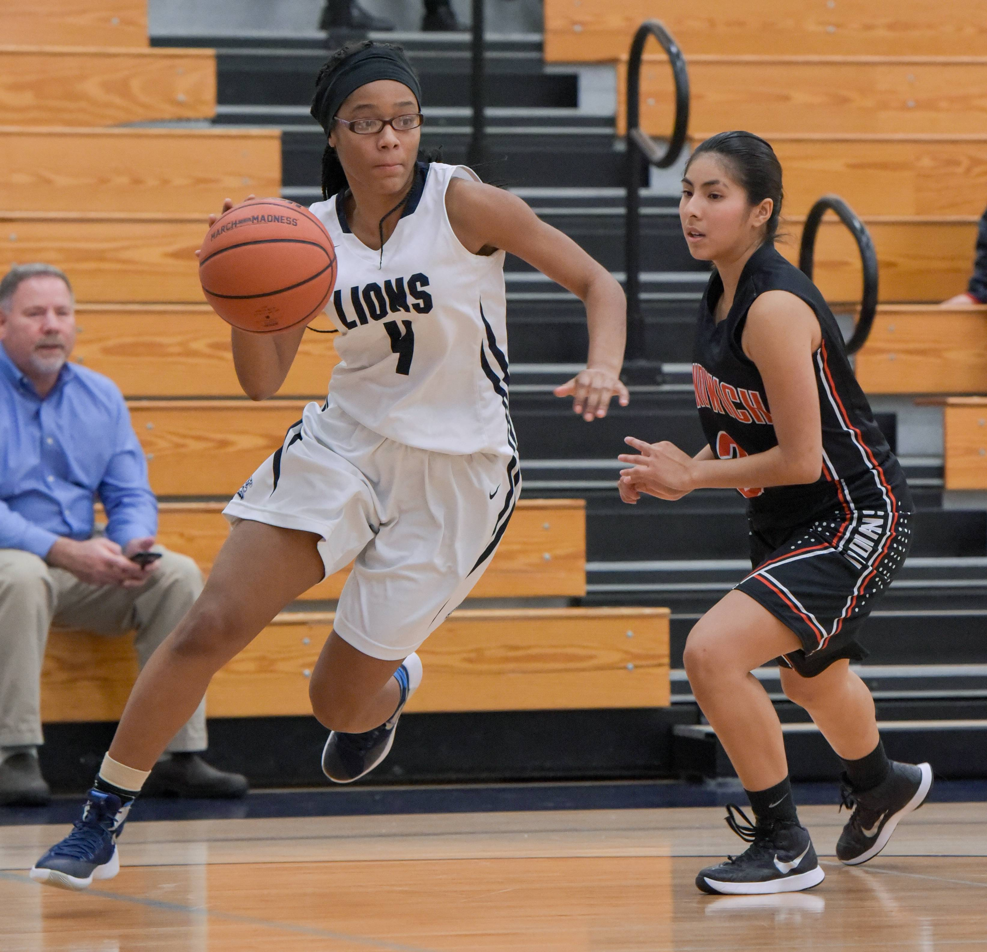 Lisle's Paige Kellie (4) drives around Sandwich's Ezbeydy Rivera (3) during girls varsity basketball on Dec. 11, 2017 in Lisle.