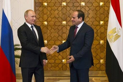 Russian President Vladimir Putin, left, and Egyptian President Abdel-Fattah El-Sissi, shake hands during their meeting in Cairo, Egypt, Monday, Dec. 11, 2017.