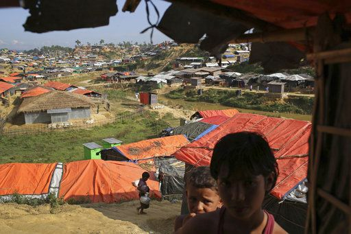 In this Sunday, Nov. 19, 2017, photo, Rohingya children stand in the shade of a tent in Kutupalong refugee camp in Bangladesh. The Associated Press has found that the rape of Rohingya women by Myanmar's security forces has been sweeping and methodical. The AP interviewed 29 women and girls who say they were raped by Myanmar's armed forces, and found distinct patterns in their accounts, their assailants' uniforms and the details of the rapes themselves. The most common attack involved groups of soldiers storming into a house, beating any children inside and then beating and gang raping the women.