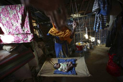 In this Sunday, Nov. 19, 2017, photo, K, 25, swings her two month old baby in her tent in Kutupalong refugee camp in Bangladesh. The Associated Press has found that the rape of Rohingya women by Myanmar's security forces has been sweeping and methodical. The AP interviewed 29 women and girls who say they were raped by Myanmar's armed forces, and found distinct patterns in their accounts, their assailants' uniforms and the details of the rapes themselves. The most common attack involved groups of soldiers storming into a house, beating any children inside and then beating and gang raping the women.