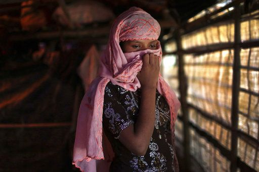 In this Sunday, Nov. 19, 2017, photo, R, 13, covers her face with her headscarf while being photographed in her tent in Kutupalong refugee camp in Bangladesh. The Associated Press has found that the rape of Rohingya women by Myanmar's security forces has been sweeping and methodical. The AP interviewed 29 women and girls who say they were raped by Myanmar's armed forces, and found distinct patterns in their accounts, their assailants' uniforms and the details of the rapes themselves. The most common attack involved groups of soldiers storming into a house, beating any children inside and then beating and gang raping the women.