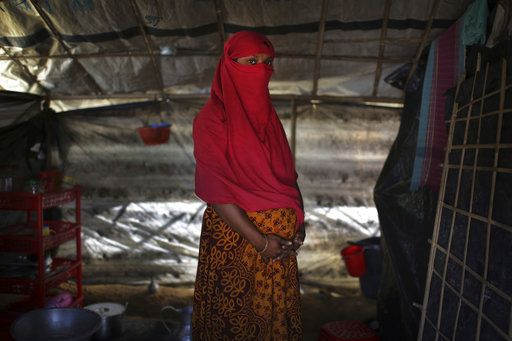 In this Monday, Nov. 20, 2017, photo, F, 22, who says she was raped by members of Myanmar's armed forces in June and again in September, clutches her hands around her pregnant belly as she is photographed in her tent in Kutupalong refugee camp in Bangladesh. The Associated Press has found that the rape of Rohingya women by Myanmar's security forces has been sweeping and methodical. The AP interviewed 29 women and girls who say they were raped by Myanmar's armed forces, and found distinct patterns in their accounts, their assailants' uniforms and the details of the rapes themselves. The most common attack involved groups of soldiers storming into a house, beating any children inside and then beating and gang raping the women.