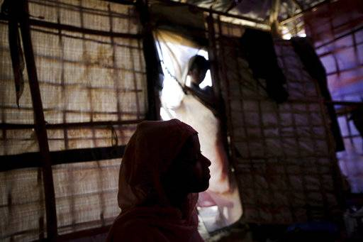 In this Sunday, Nov. 19, 2017, photo, R, 13, is seen in silhouette as she speaks to The Associated Press in her tent in Kutupalong refugee camp in Bangladesh. The Associated Press has found that the rape of Rohingya women by Myanmar's security forces has been sweeping and methodical. The AP interviewed 29 women and girls who say they were raped by Myanmar's armed forces, and found distinct patterns in their accounts, their assailants' uniforms and the details of the rapes themselves. The most common attack involved groups of soldiers storming into a house, beating any children inside and then beating and gang raping the women.