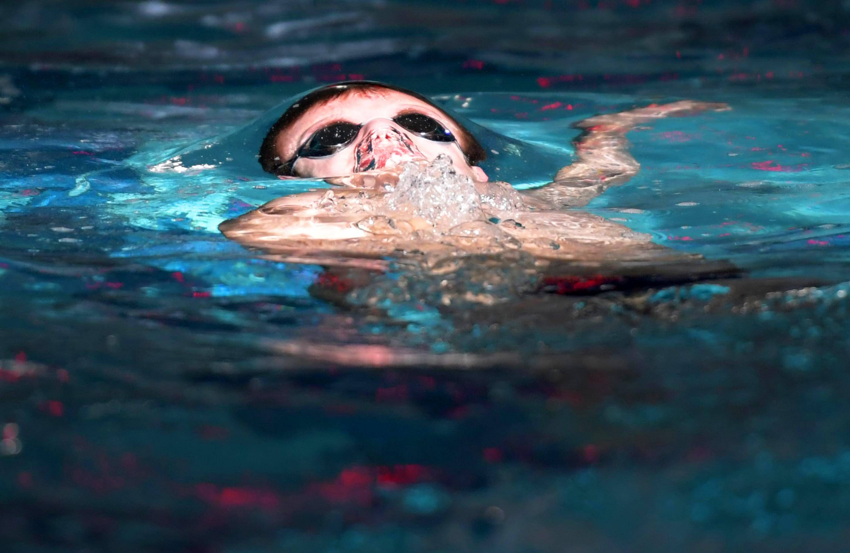 Bartlett High School's Truman Jacobson rises out of the water in a beam of window light during the backstroke leg of the 200-yard medley relay Saturday at the Wildcat Relays hosted by West Chicago and Batavia at West Chicago's Community High School.