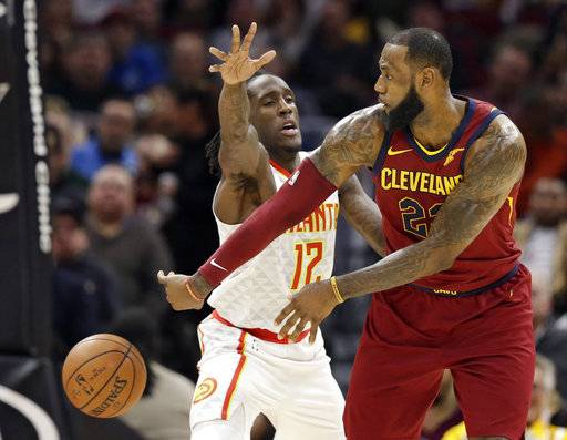 Cleveland Cavaliers' LeBron James, right, passes against Atlanta Hawks' Taurean Prince in the first half of an NBA basketball game, Tuesday, Dec. 12, 2017, in Cleveland.