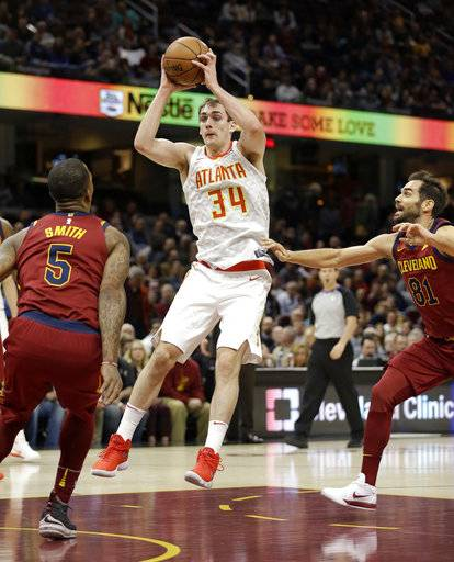 Atlanta Hawks' Tyler Cavanaugh (34) drives between Cleveland Cavaliers' JR Smith (5) and Cleveland Cavaliers' Jose Calderon (81), from Spain, in the first half of an NBA basketball game, Tuesday, Dec. 12, 2017, in Cleveland.