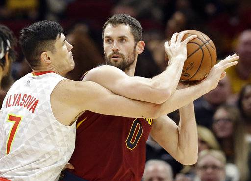 Cleveland Cavaliers' Kevin Love, right, looks to pass against Atlanta Hawks' Ersan Ilyasova (7), from Turkey, in the first half of an NBA basketball game, Tuesday, Dec. 12, 2017, in Cleveland.