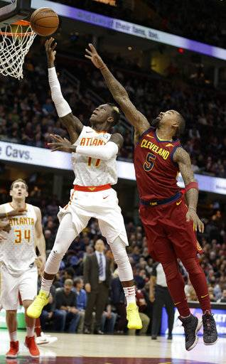 Atlanta Hawks' Dennis Schroder (17), from Germany, drives to the basket against Cleveland Cavaliers' JR Smith (5) in the first half of an NBA basketball game, Tuesday, Dec. 12, 2017, in Cleveland.