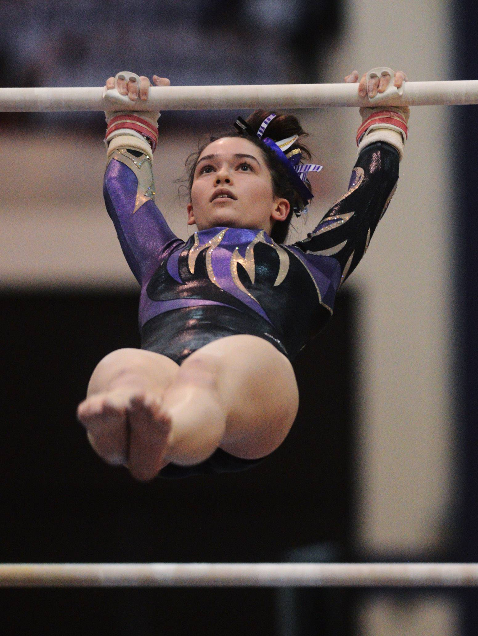 Rolling Meadows' Jenna Byrne competes on the uneven parallel bars during Wednesday's home gymnastics meet with Fremd and Prospect.