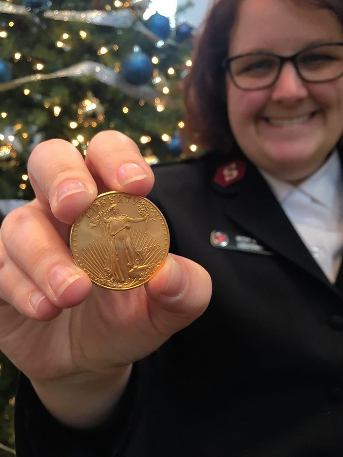 Lt. Betsy Clark of The Salvation Army Tri-City Corps receives one gold coin in a red kettle during the Colonial Cafe Match Day Dec. 9.