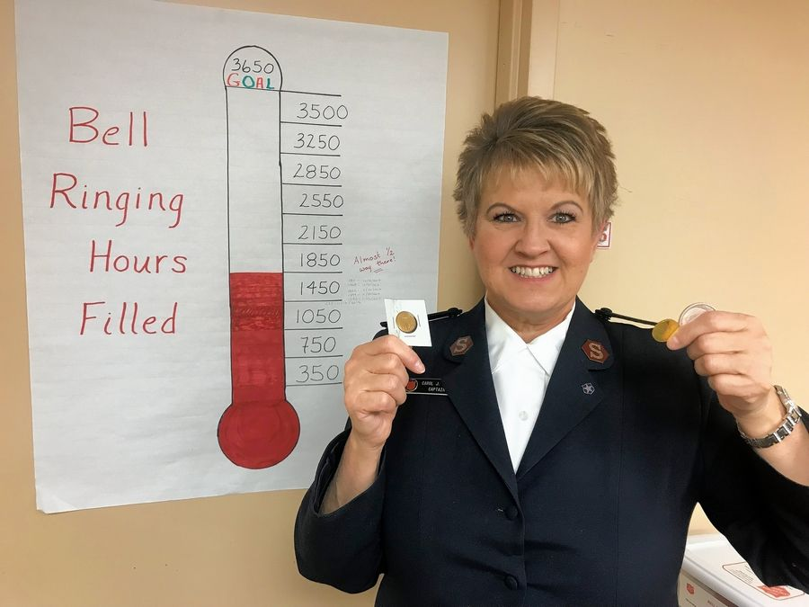 Captain Carol Lewis of The Salvation Army McHenry County Corps receives three gold and silver coins in the red kettles during the Colonial Cafe Match Day Dec. 9.
