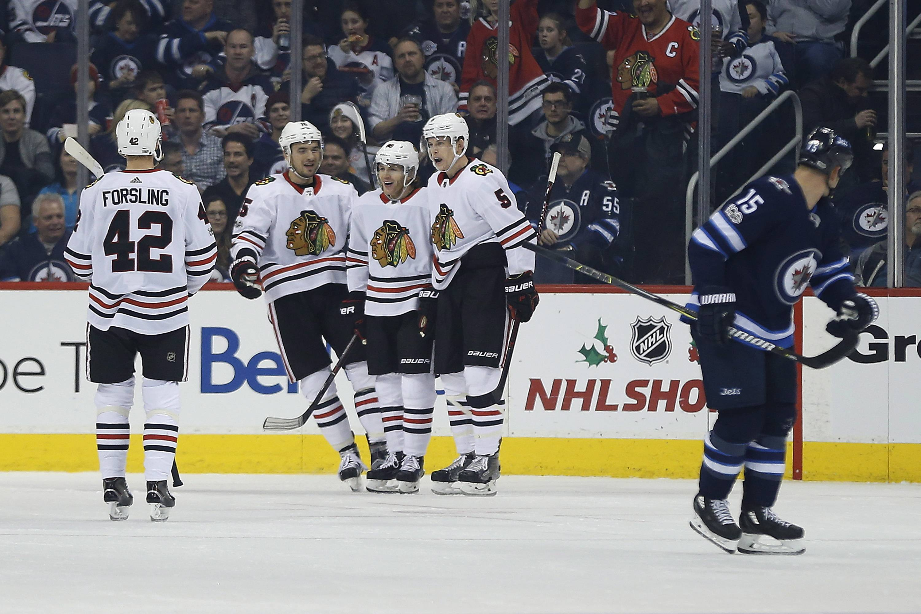 From left to right, Chicago Blackhawks' Gustav Forsling (42), Artem Anisimov (15), Patrick Kane (88) and Connor Murphy (5) celebrate Kane's goal against the Winnipeg Jets during second-period NHL hockey game action in Winnipeg, Manitoba, Thursday, Dec. 14, 2017. (John Woods/The Canadian Press via AP)