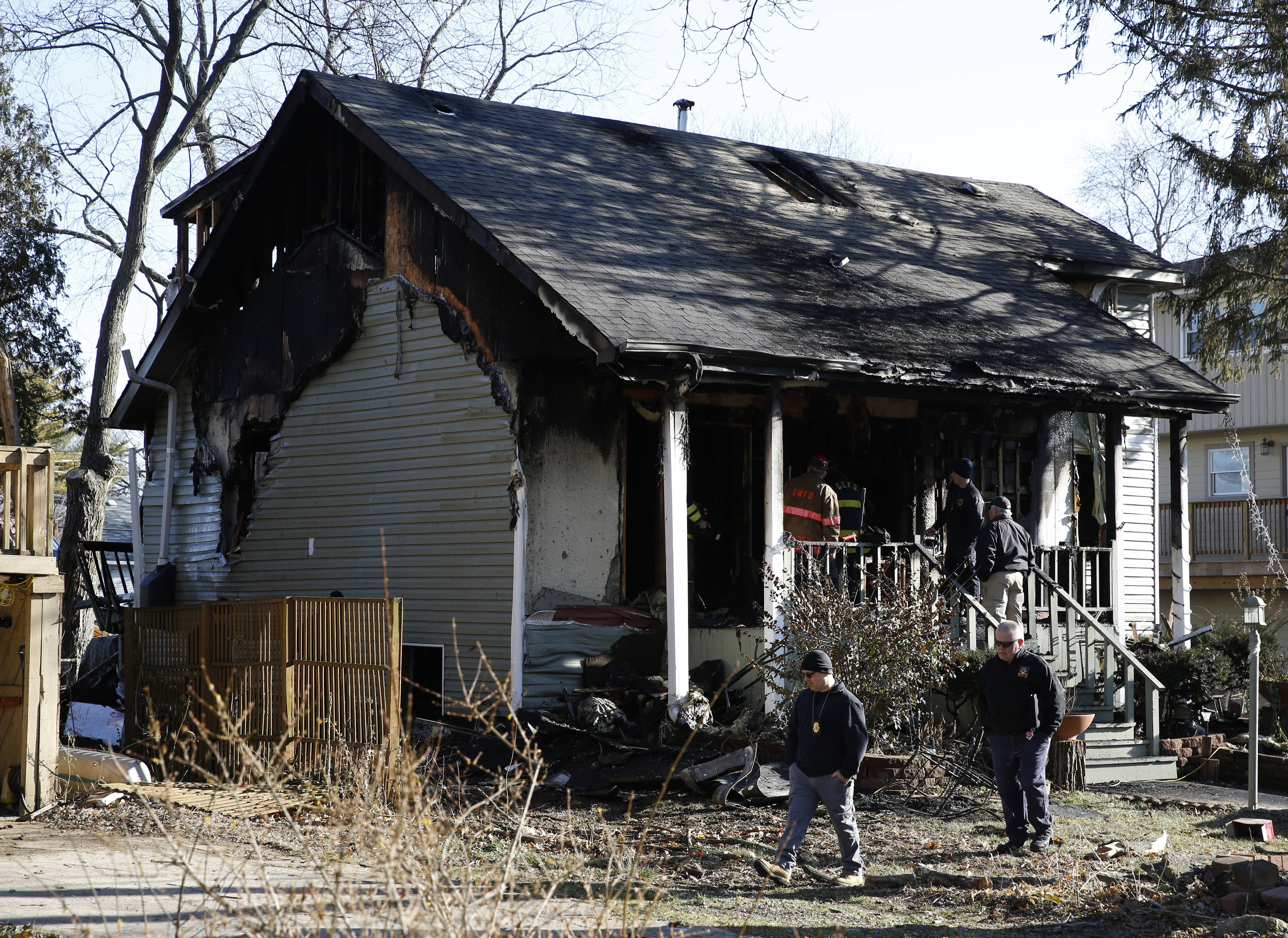 Officials investigate the aftermath of a fire in the 4700 block of Dumoulin Avenue in Lisle which sent two adults and four children ages 3-12 to the hospital.