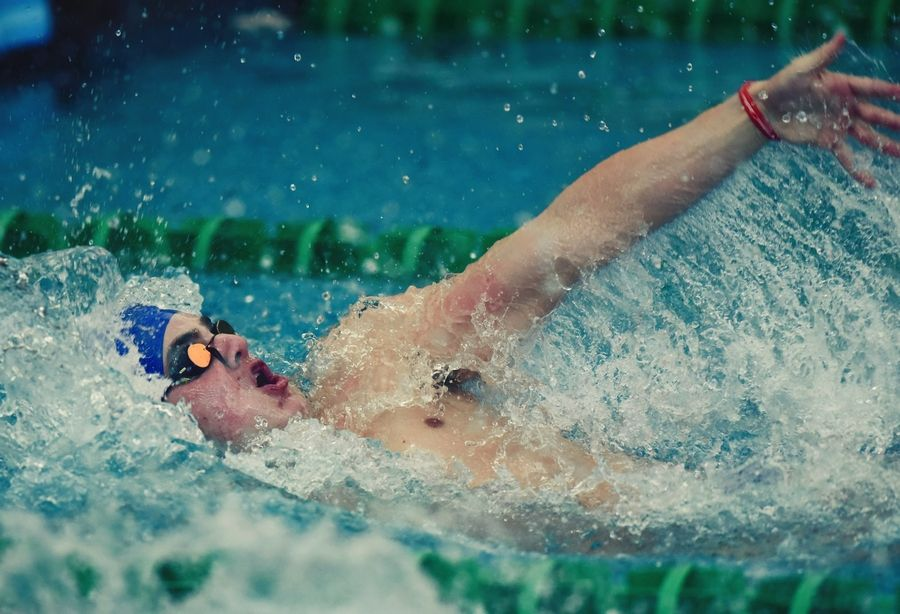 Warren's Brian Tabourot swim backstroke in the 200-yard medley relay during the Lake County Invitational at Stevenson on Saturday.