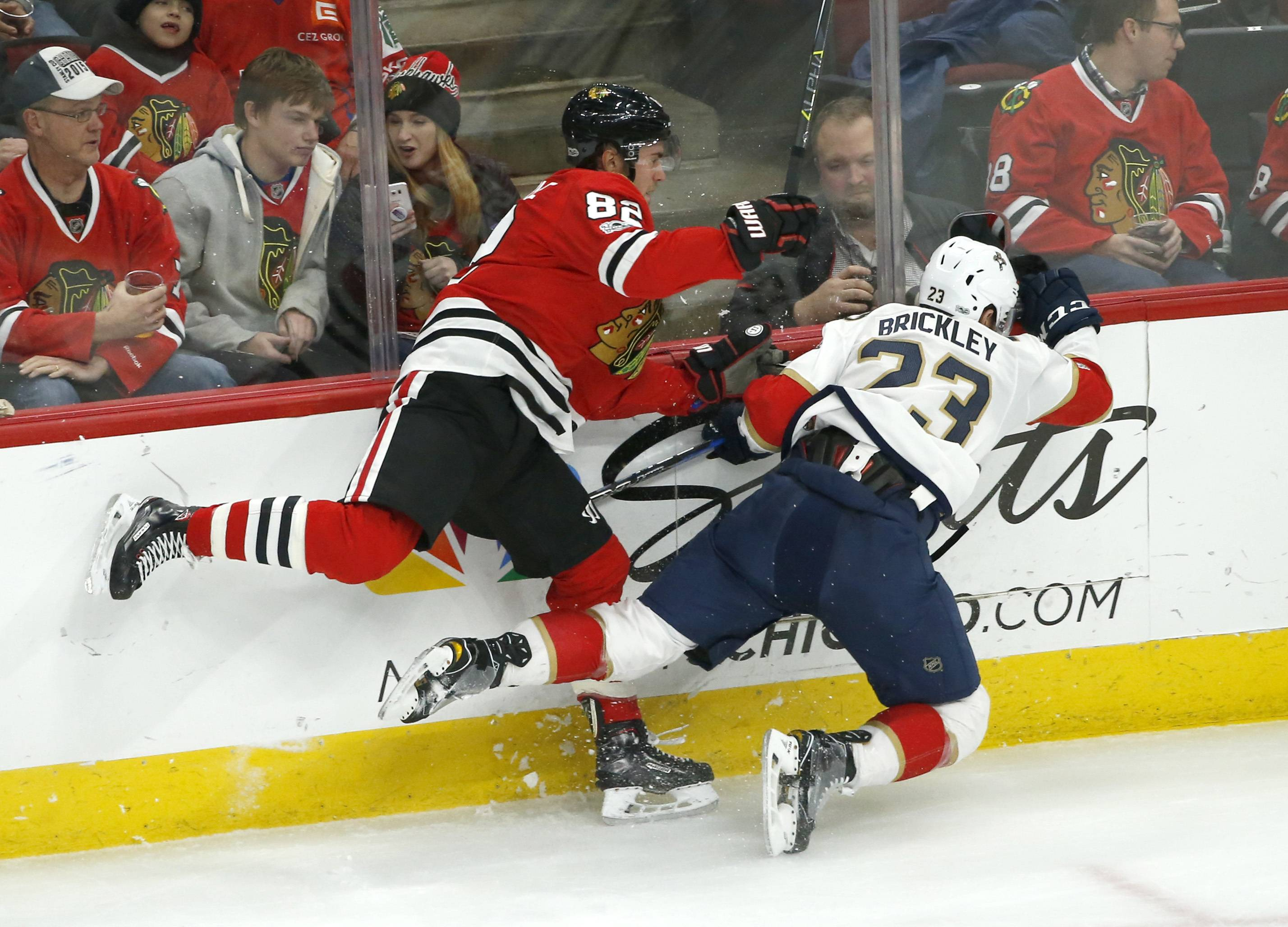 Chicago Blackhawks' Jordan Oesterle, left, checks Florida Panthers' Connor Brickley, right, along the boards during the second of an NHL hockey game Tuesday, Dec. 12, 2017, in Chicago. (AP Photo/Charles Rex Arbogast)