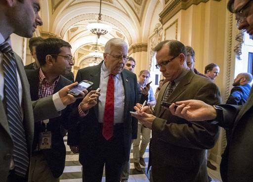 Reporters interview Sen. Mike Enzi, R-Wyo., chairman of the Senate Budget Committee, as arrives to meet with House Ways and Means Committee Chairman Kevin Brady, R-Texas, at the Capitol to advance the GOP tax bill, in Washington, Friday, Dec. 15, 2017. (AP Photo/J. Scott Applewhite)