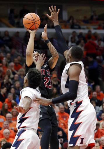 New Mexico State guard Zach Lofton, center, goes up to shoot against Illinois guard Trent Frazier, left, and forward Leron Black during the first half of an NCAA college basketball game Saturday, Dec. 16, 2017, in Chicago. (AP Photo/Nam Y. Huh)