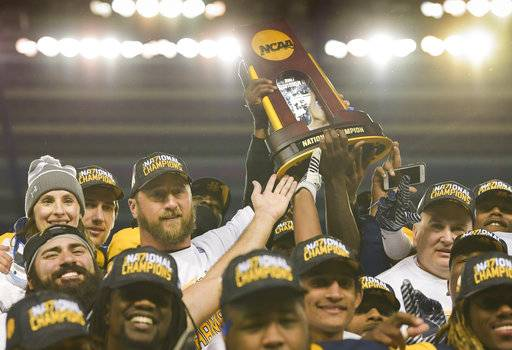 Head coach Colby Carthel (with trophy) and his Texas A&M-Commerce Lions celebrate their NCAA Division II college football championship against West Florida in Kansas City, Kan., Saturday, Dec. 16, 2017. (AP Photo/Reed Hoffmann)